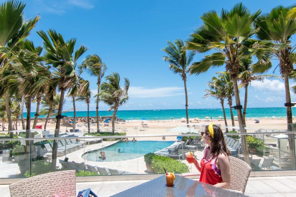 Girl having a cocktail and looking out onto Condado beach, San Juan, Puerto Rico