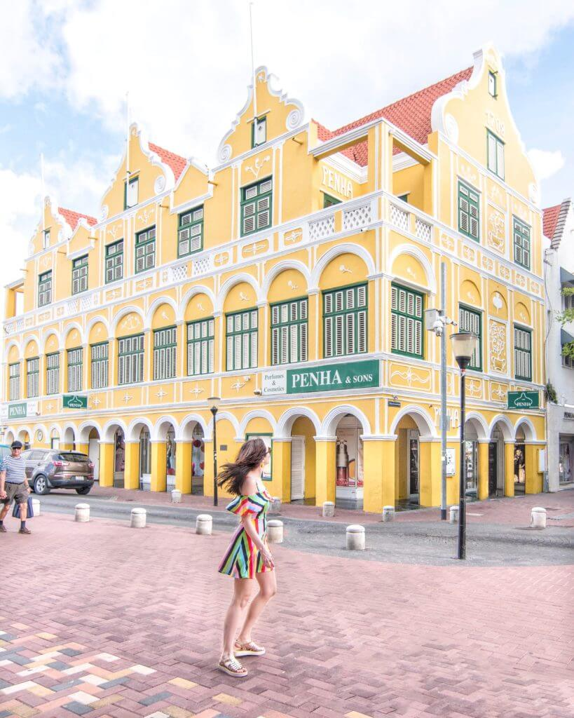 Woman walking in front of yellow building in Willemstad, Curaçao
