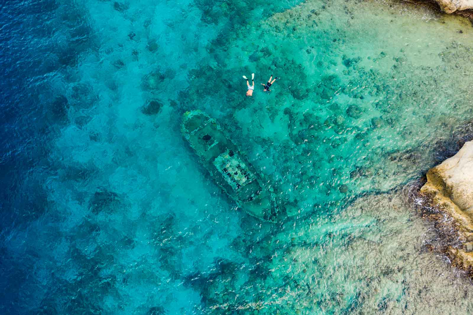 Overhead view of Tugboat Beach in Aruba, showing two people snorkeling in the water