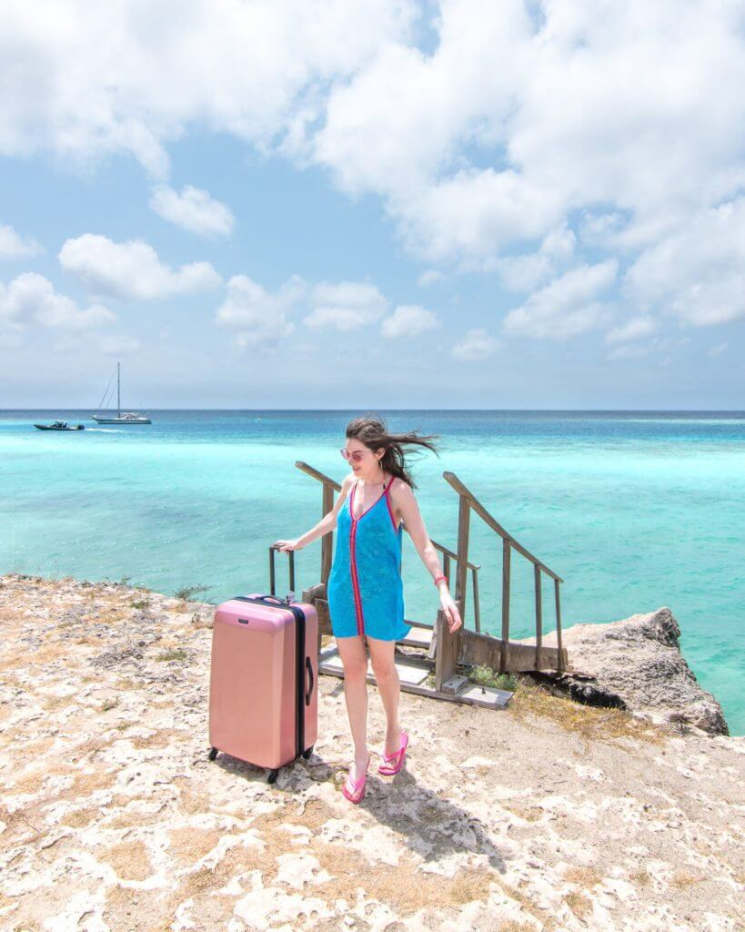 Woman with suitcase standing next to clear blue water in Aruba
