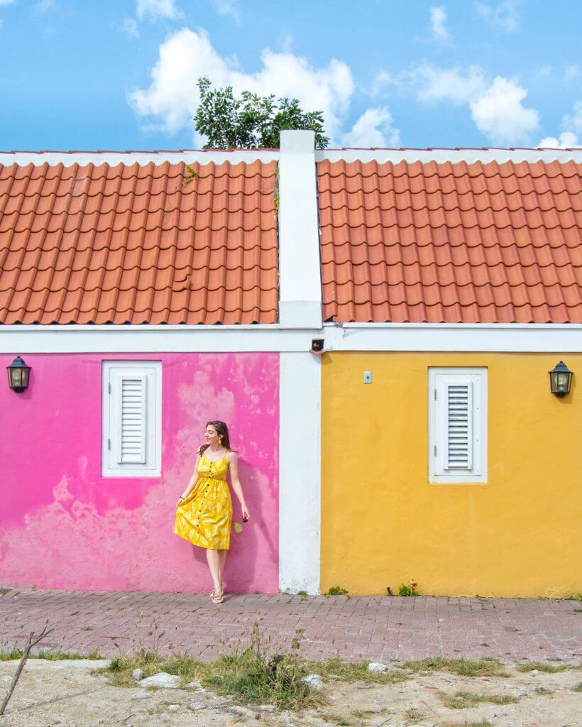 Woman in yellow dress standing between pink and yellow building in Willemstad, Curaçao