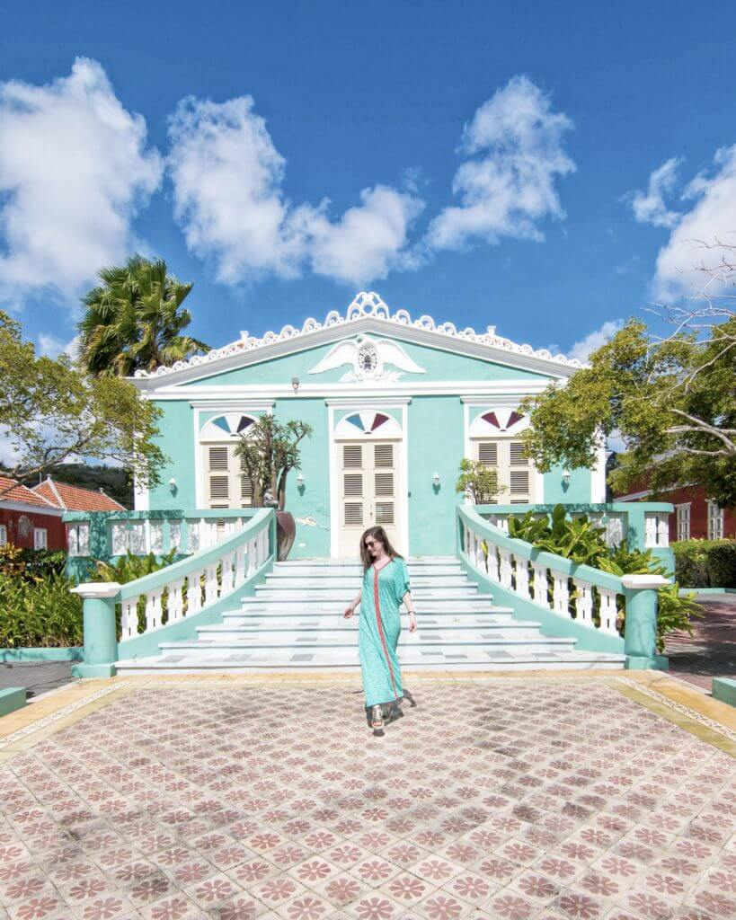 woman in turquoise dress walking in front of matching color historic building in Willemstad, Curaçao