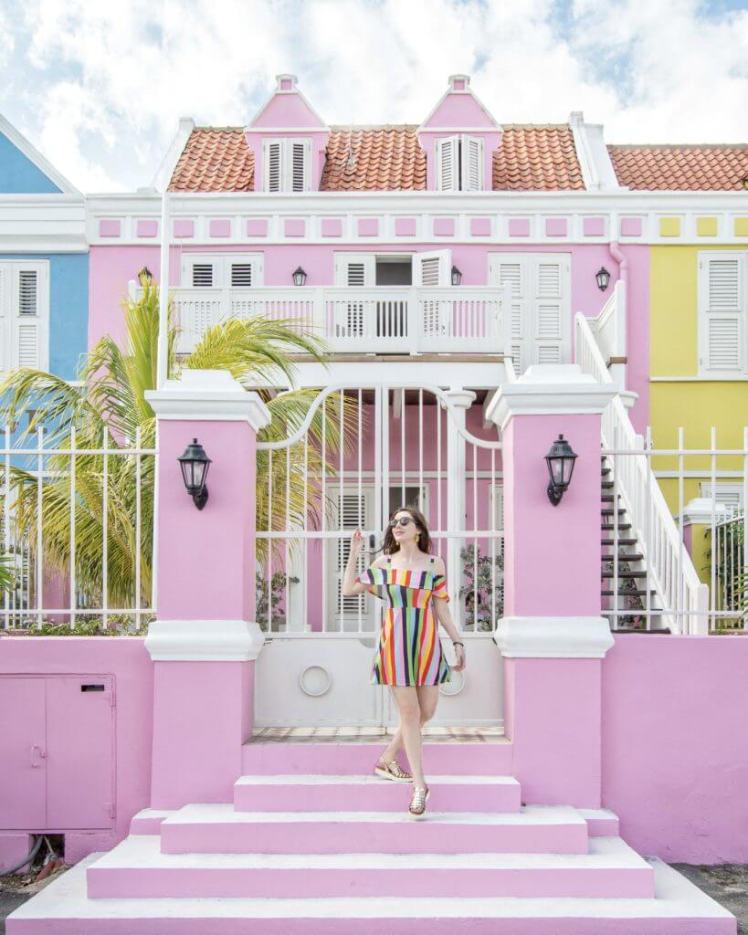 Woman walking in front of pink building in Willemstad, Curaçao