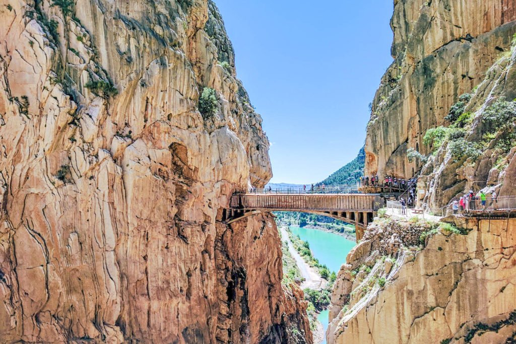 A view of a bridge hanging between two gigantic rocks as part of the Caminito del Rey.