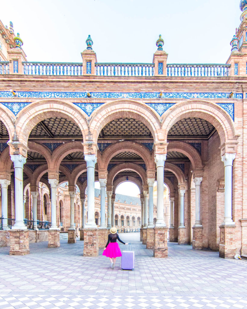 A girl in a pink tutu standing in front of some of the famous arches at the Plaza de España in Seville.