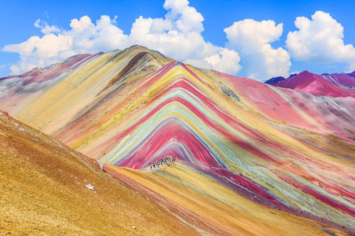 People hiking along the base of Rainbow Mountain in Peru.