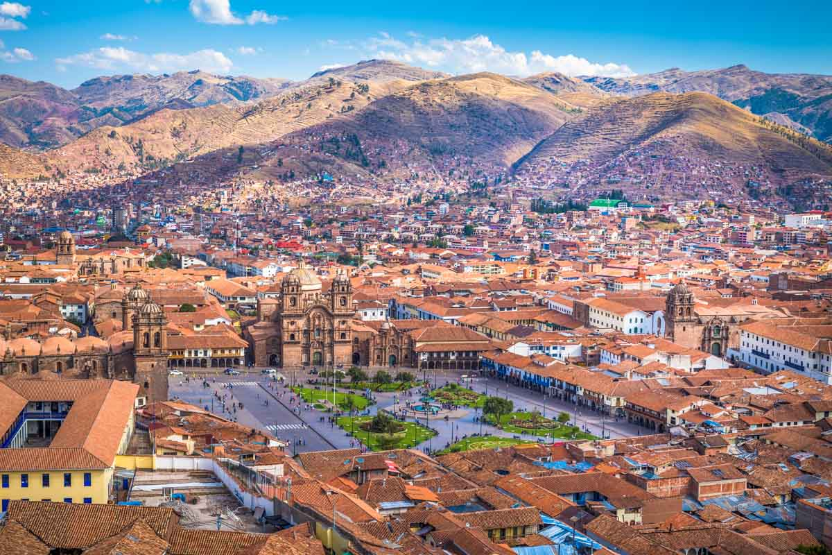 View of the city of Cusco, showing the Plaza de Armas, surrounding buildings, and the rolling hills outside the city.