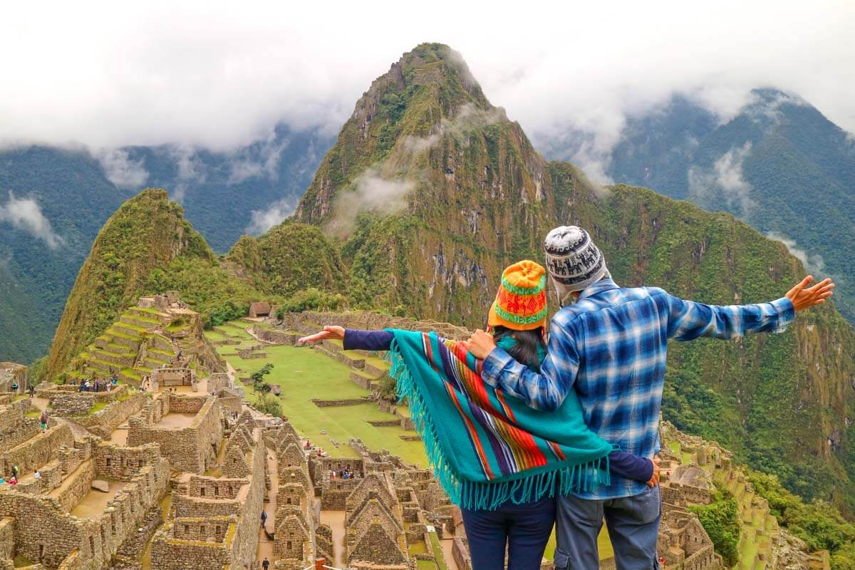 Couple with their backs facing the camera looking out over Machu Picchu.