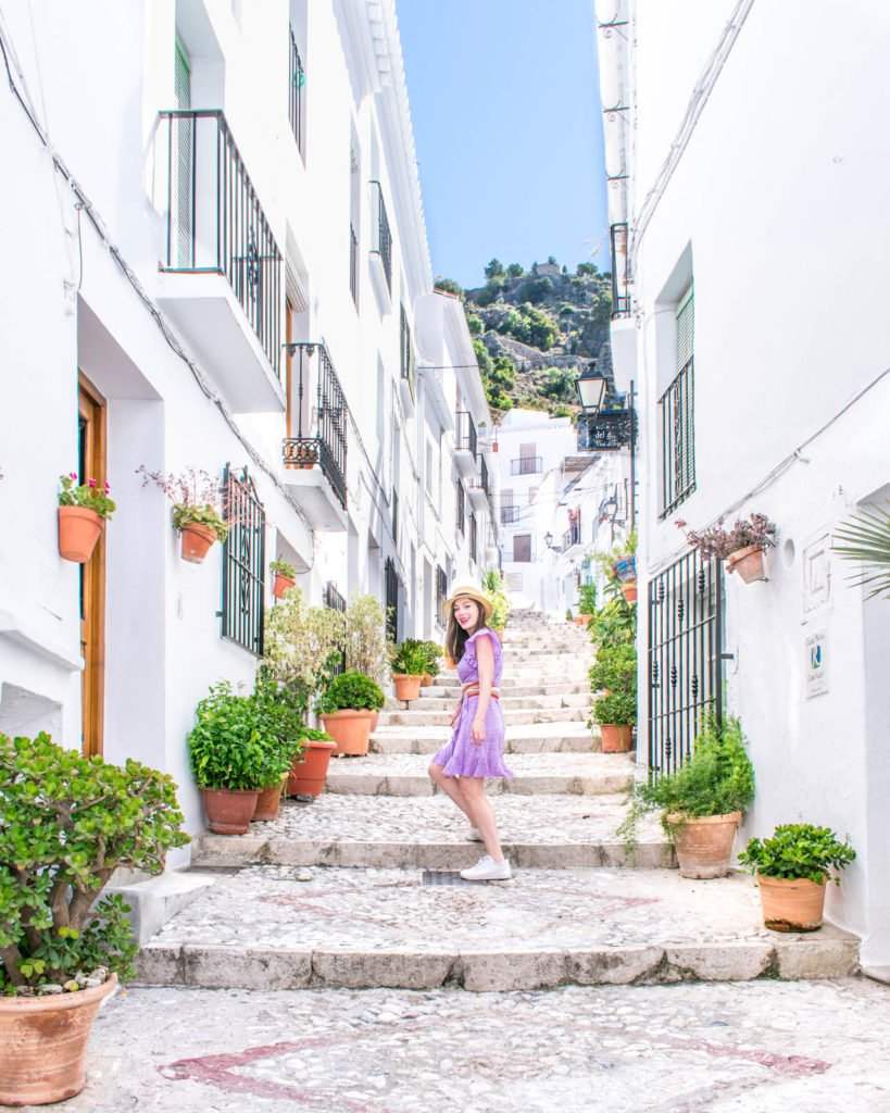 A girl standing on stairs surrounded by beautiful white homes in Frigiliana, Spain.
