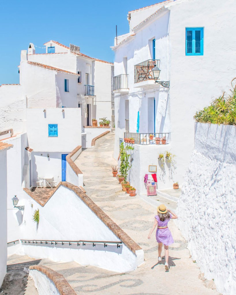 A girl walking down a beautiful street in the village of Frigiliana, surrounded by white houses.