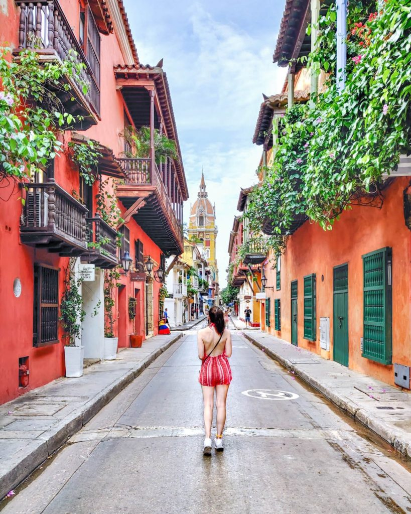 Famous street in Cartagena with colonial homes and yellow cathedral in the background