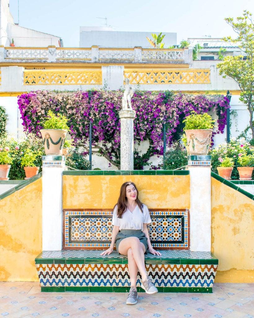 Girl sitting on colorful tile bench at the Casa de Pilatos
