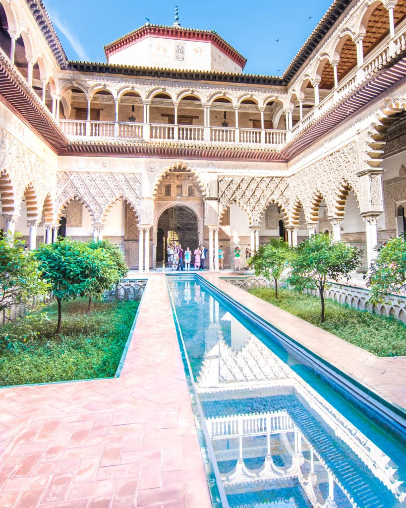 View of facade of the Real Alcázar of Seville with reflecting pool