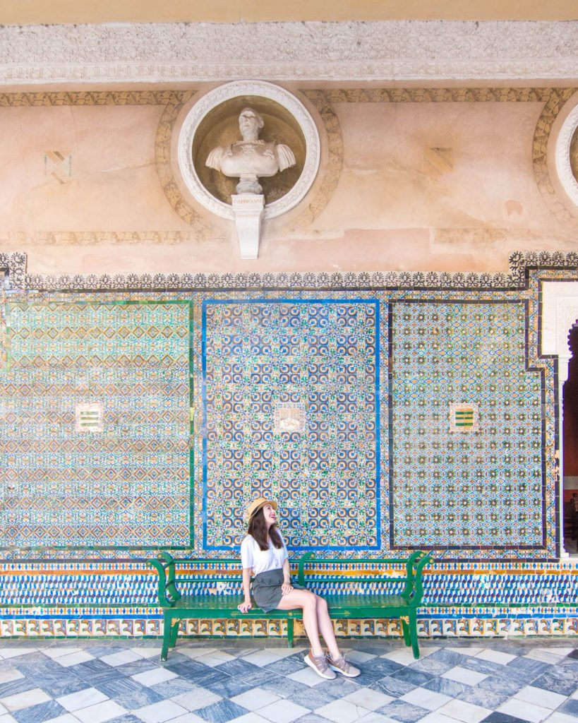 Girl sitting on bench in front of tiled wall at the Casa de Pilatos