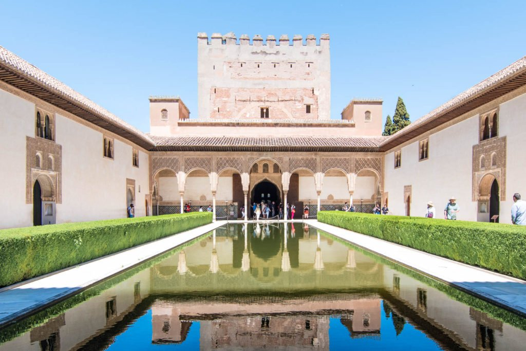 A view of the Alhambra's facade with reflection in pool of water.