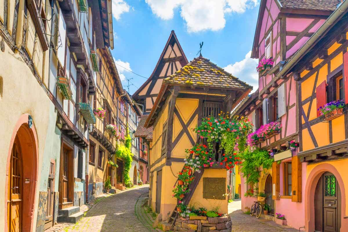 Photo of colorful homes lining historic street in Eguisheim, Alsace Region, France