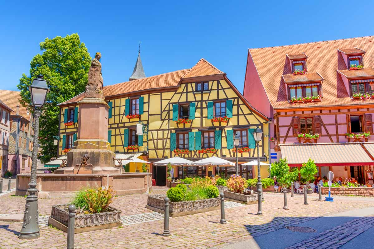 Fountain and colorful historic homes in Ribeauvillé, Alsace Region, France