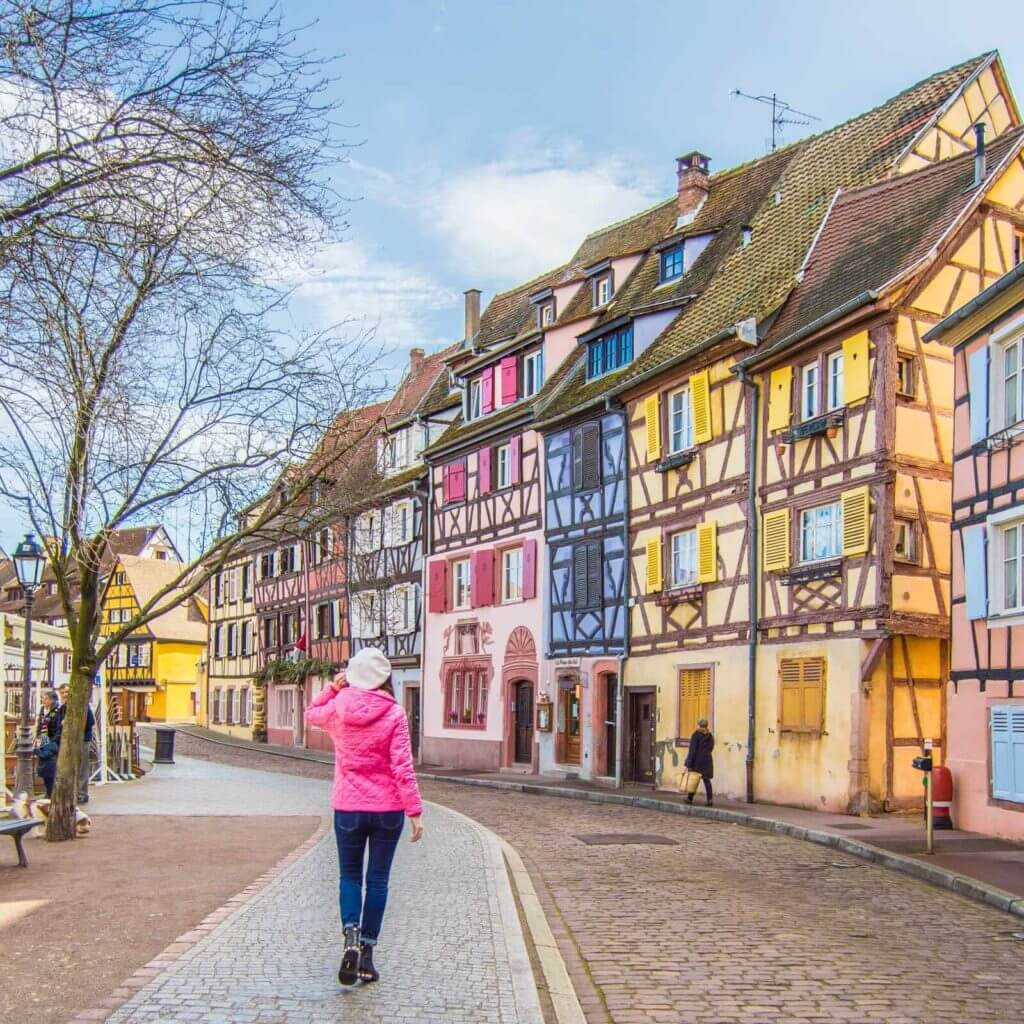 woman walking next to colorful half-timbered houses in Colmar, Alsace region, France