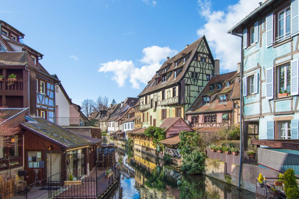 A view of the Little Venice canal area in Colmar, overlooking the water with colorful timbered houses in the distance.