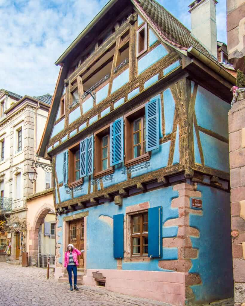 Woman walking in front of historic home in Riquewihr, France