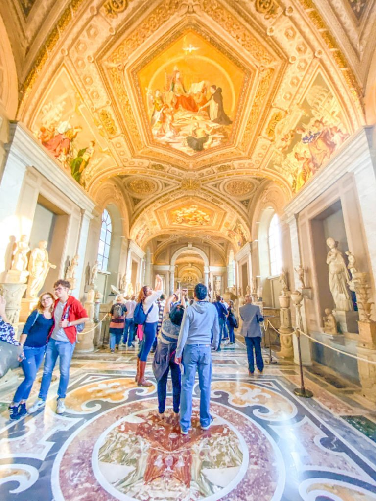 The Gallery of the Candelabra at the Vatican, with a gold ceiling and sculptures lining the walls