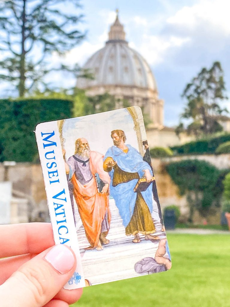 Holding out a ticket to the Vatican Museums in front of the Vatican
