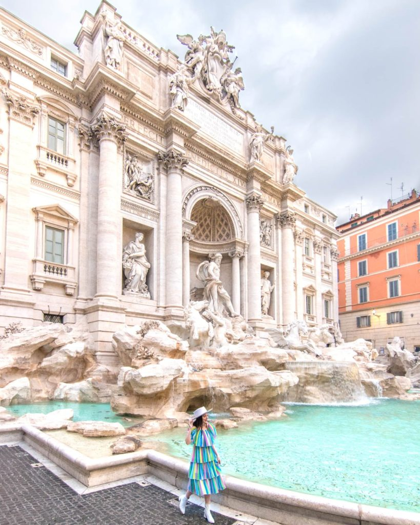 A girl in a colorful dress is walking in front of the Trevi Fountain in Rome
