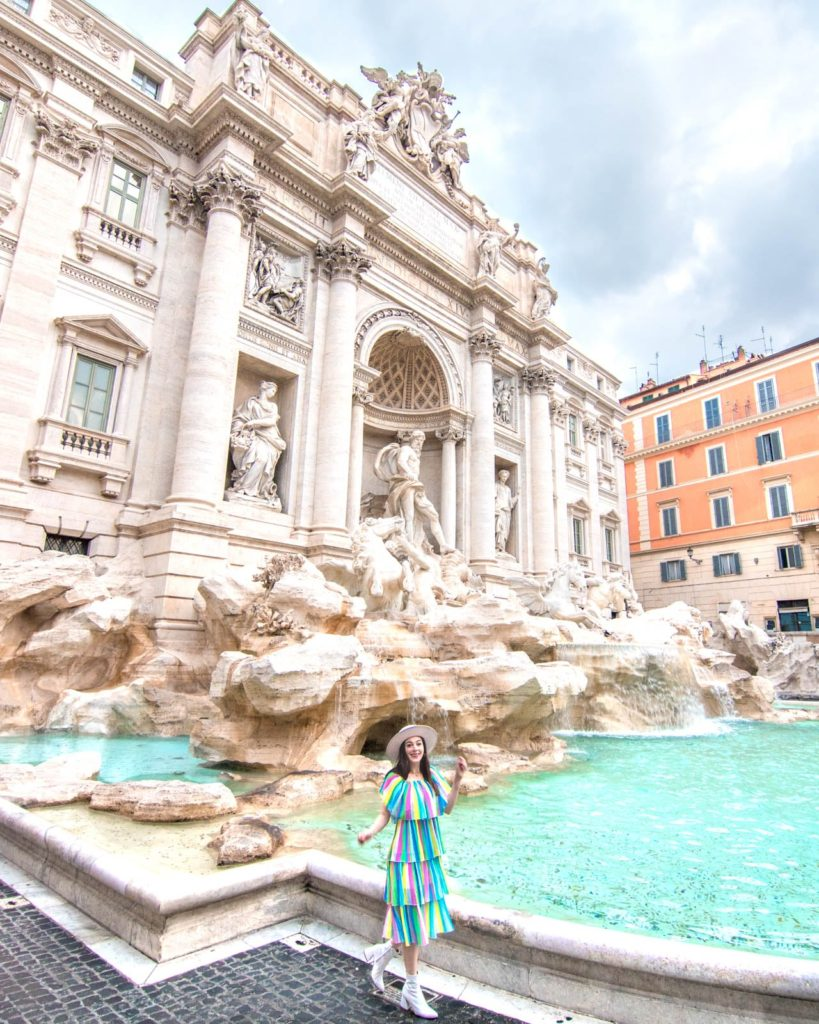 A girl in a colorful maxi dress walks in front of the Trevi Fountain in Rome, looking at the camera