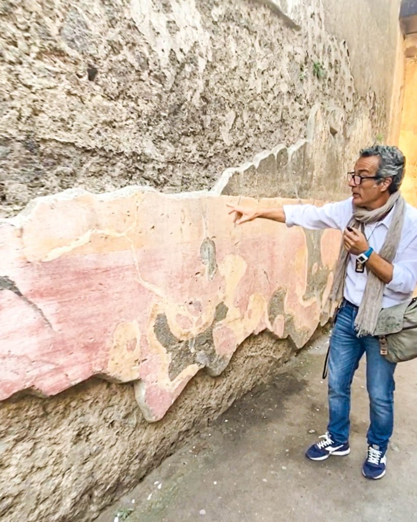 Guide pointing out graffiti wall at Pompeii