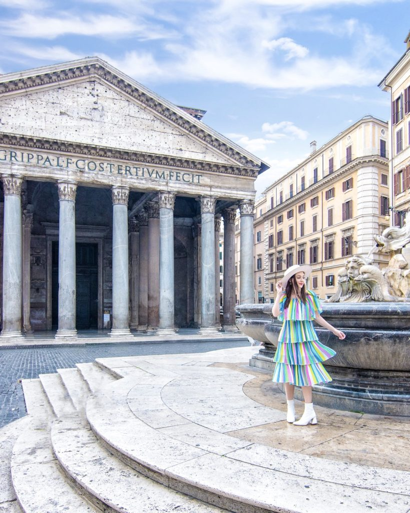 A girl in a colorful dress standing in front of the Pantheon in Rome