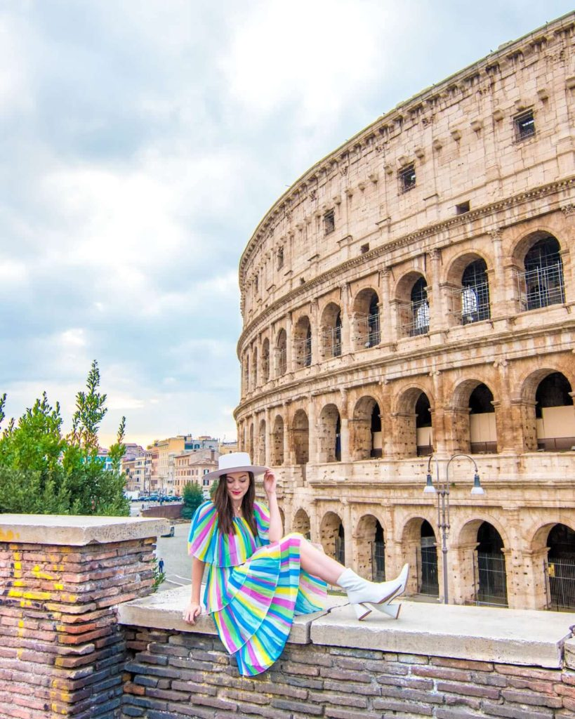 A girl sits on a ledge in front of the Colosseum in Rome