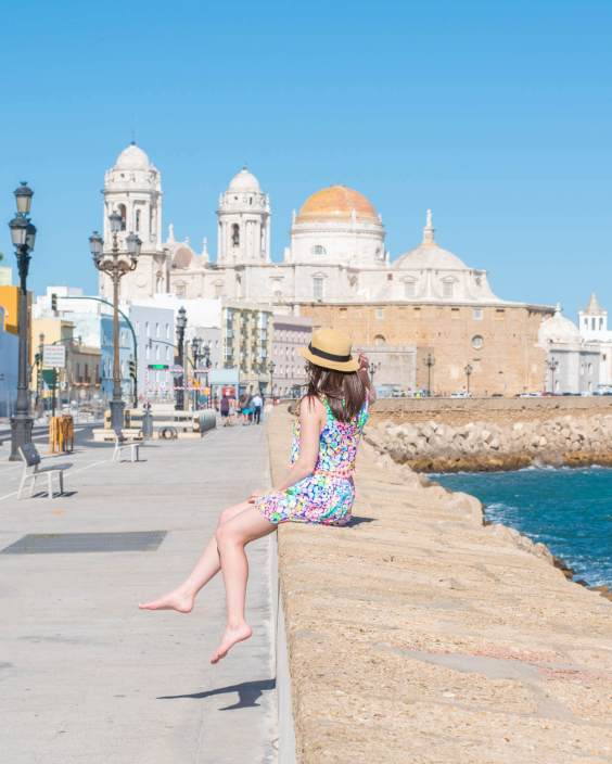 Woman sitting on ledge next to the ocean with Cadiz Cathedral in the background