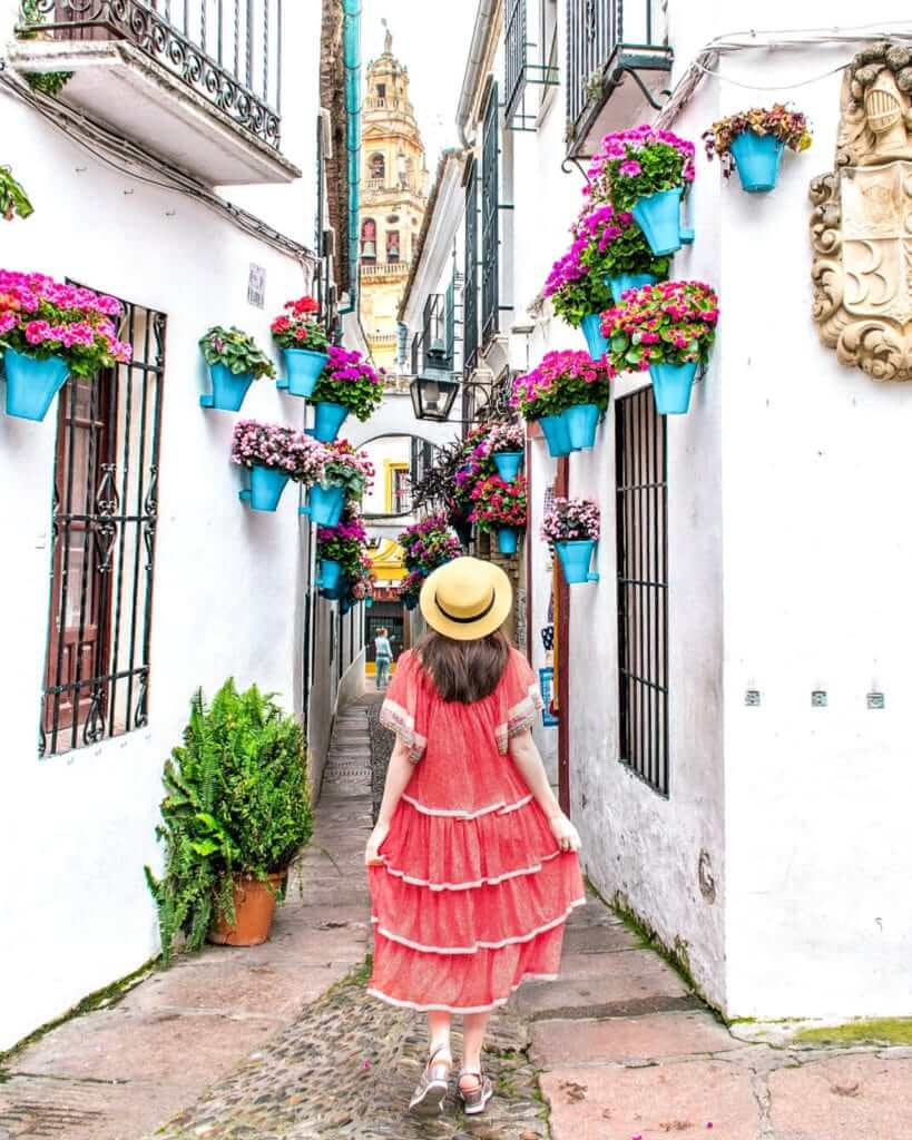 Woman walking along the most beautiful street in Cordoba: Calleja de las Flores