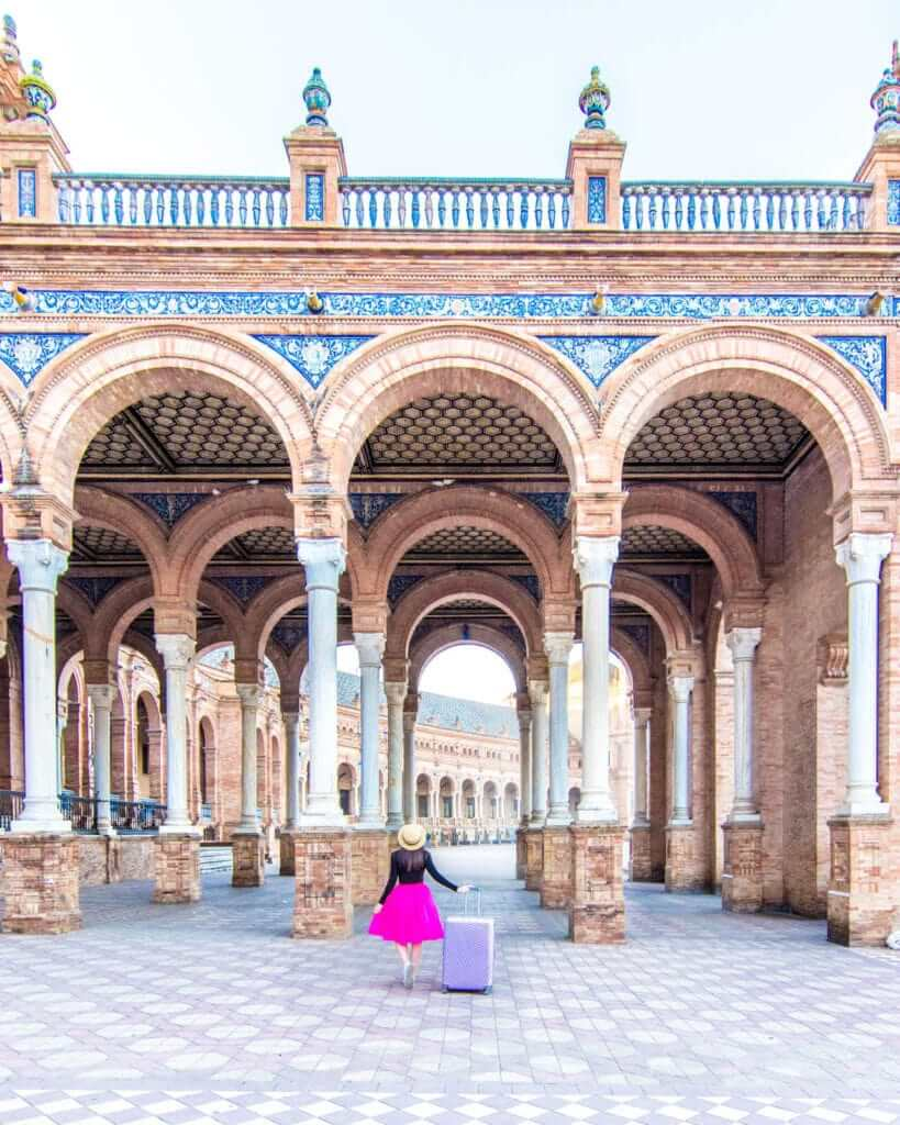 Woman standing under arches at the Plaza de España in Seville