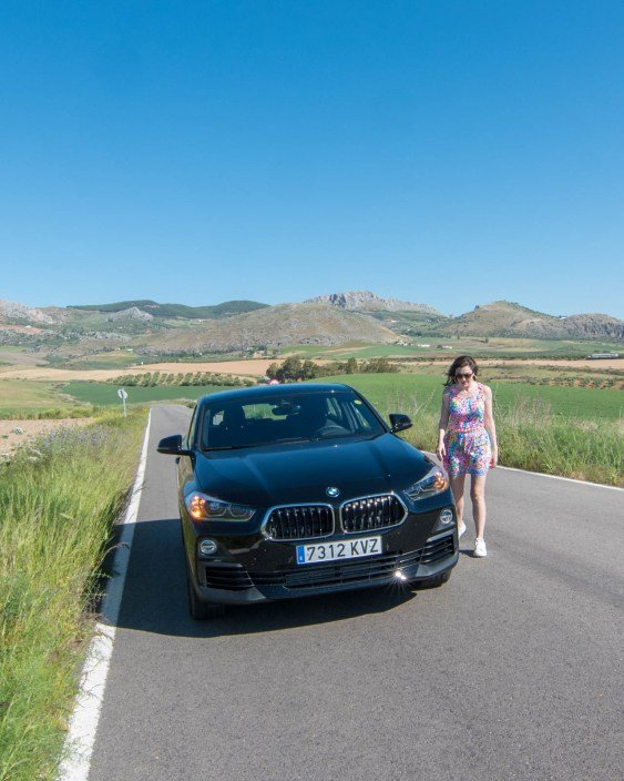 Woman standing next to black BMW on the road surrounded by green fields in Spain