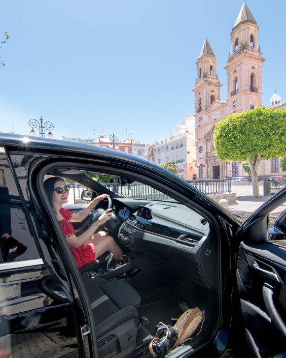 Woman driving black car in front of Cadiz Cathedral