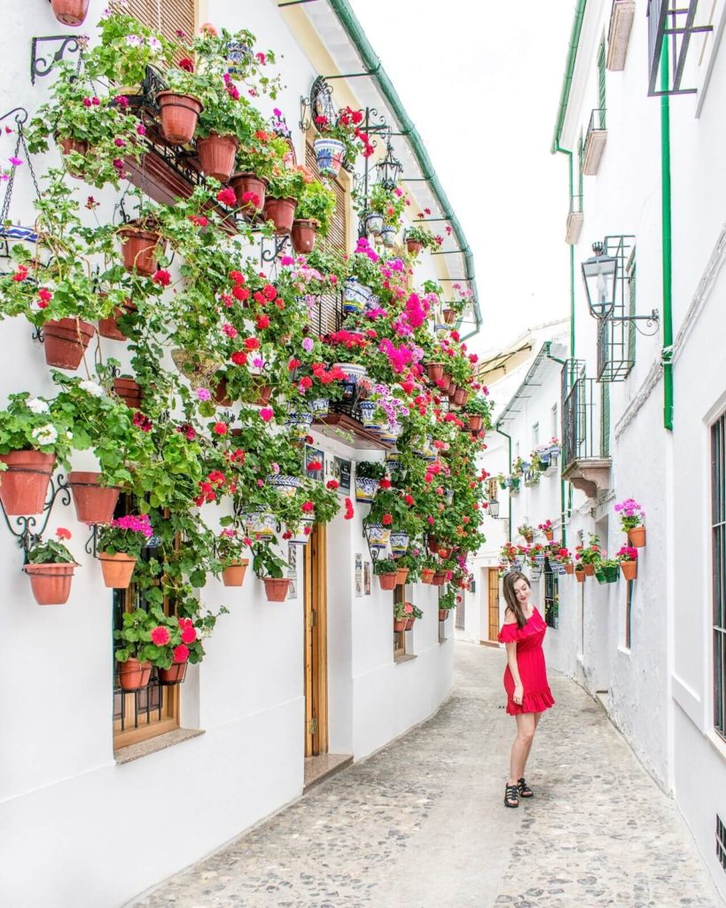 Girl standing in flower-lined street with white houses in Priego de Córdoba, Spain.