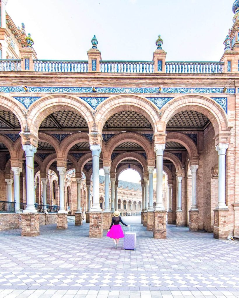 Girl standing with suitcase under an archway at María Luisa Park in Seville, Spain.