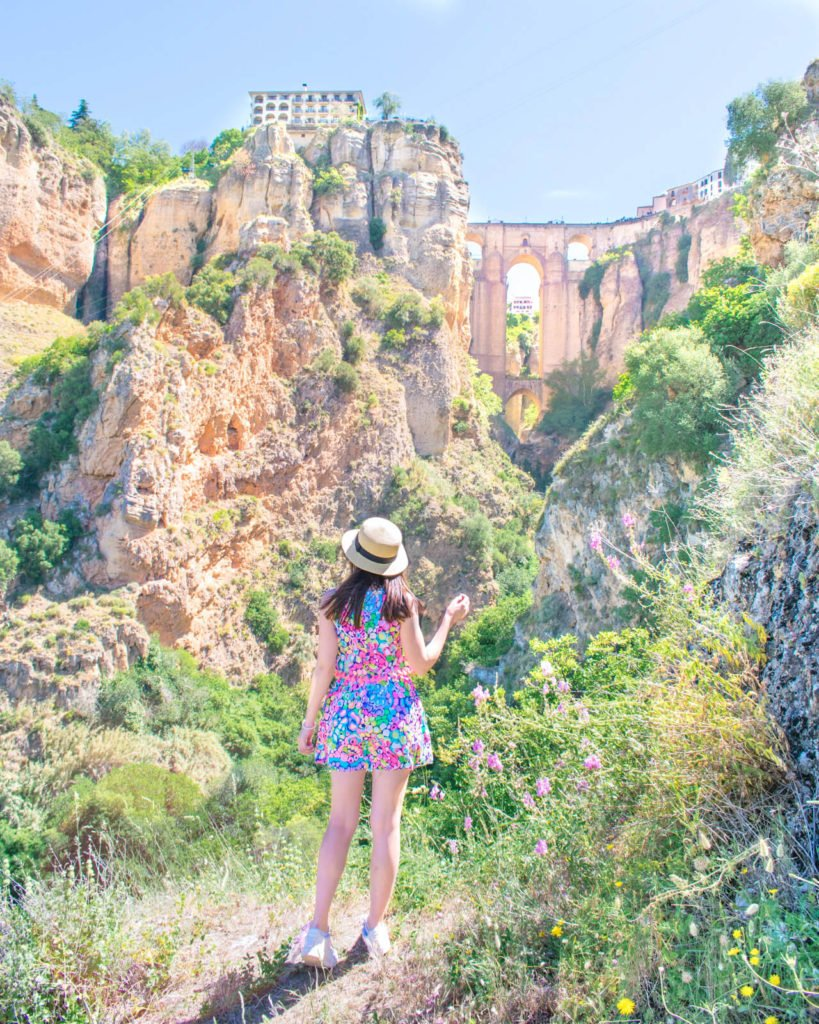 Girl standing in front of a view of Ronda, Spain with a bridge in the distance.