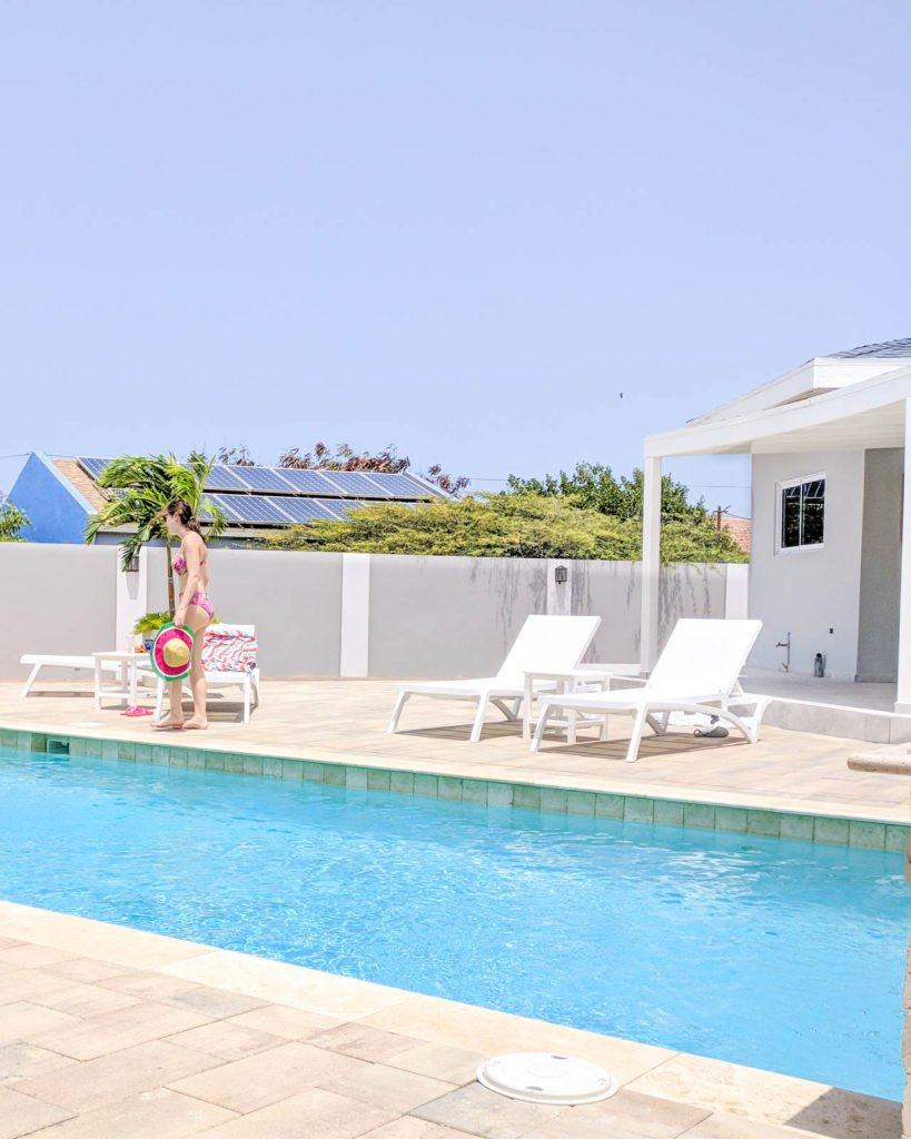 Girl walking in front of pool at Airbnb in Aruba