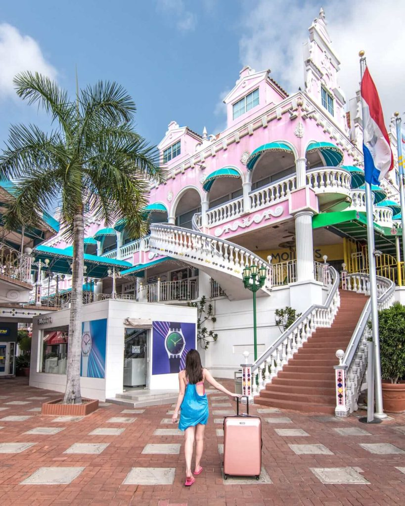 Girl with suitcase standing in front of pink shopping building in Aruba