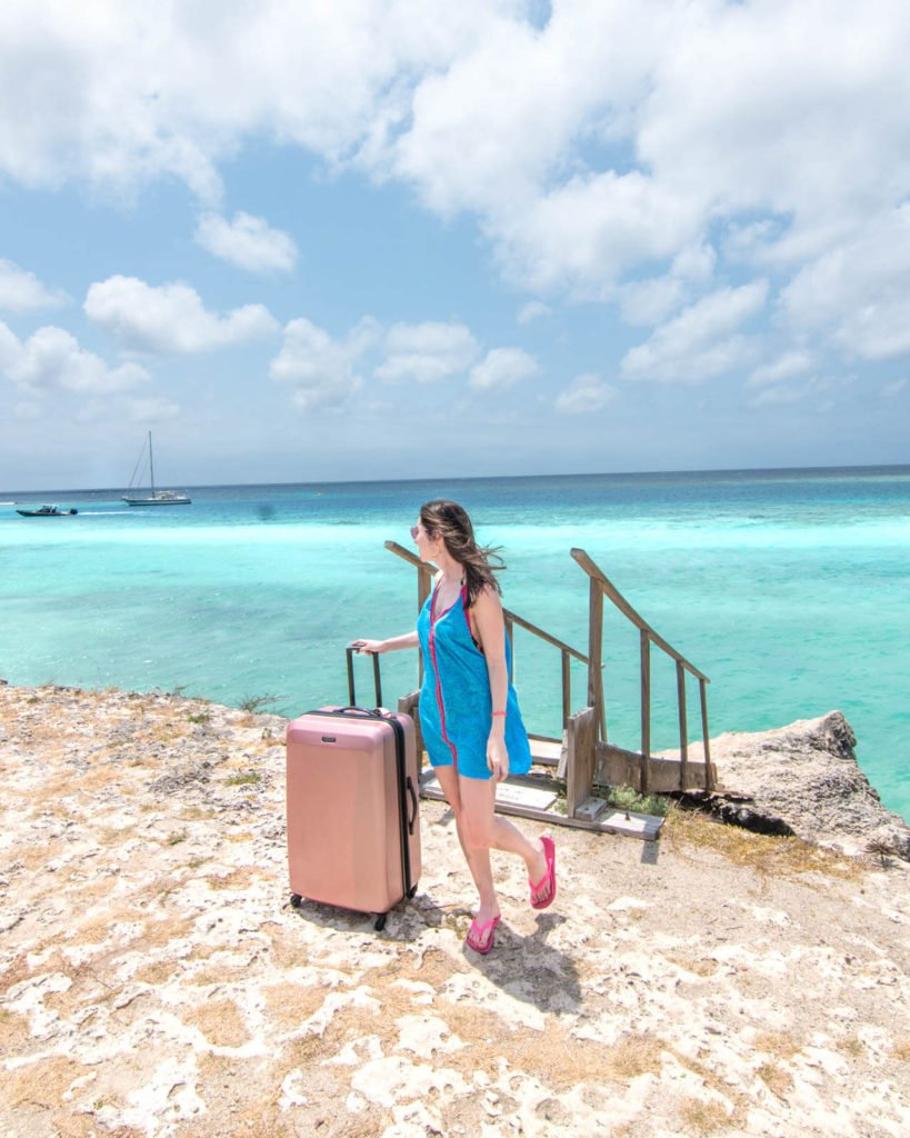 Girl walking with suitcase in front of blue Caribbean water in Aruba