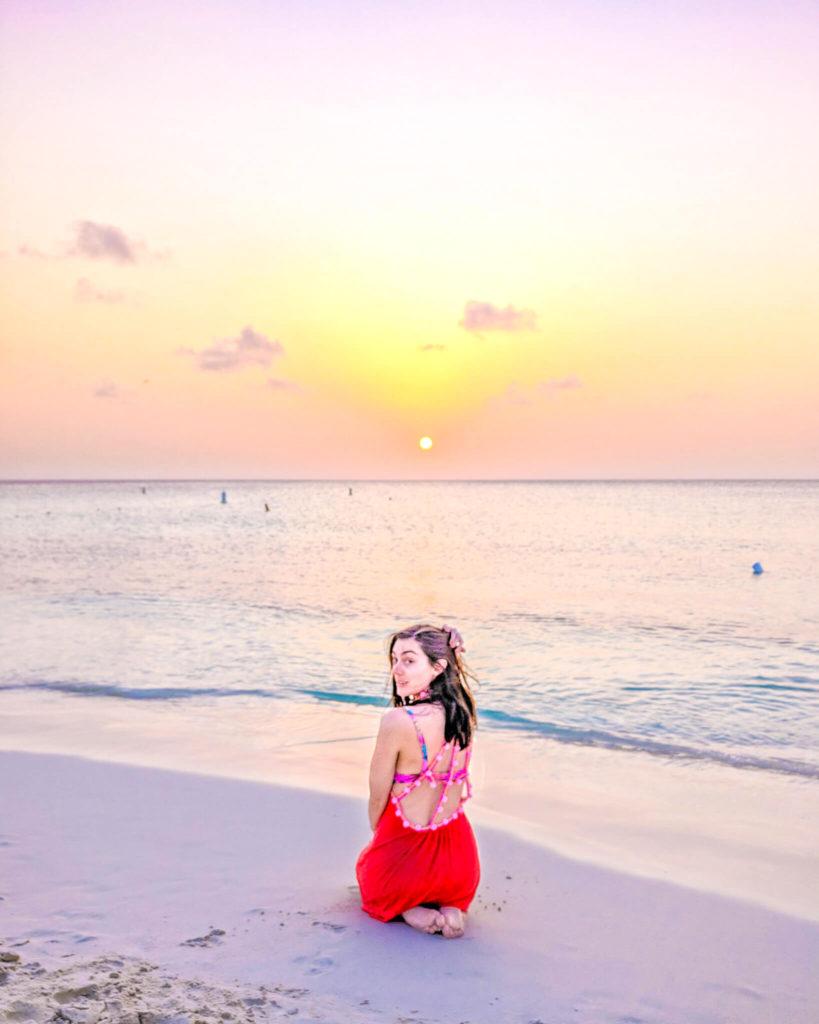 Girl sitting on beach in Aruba at sunset