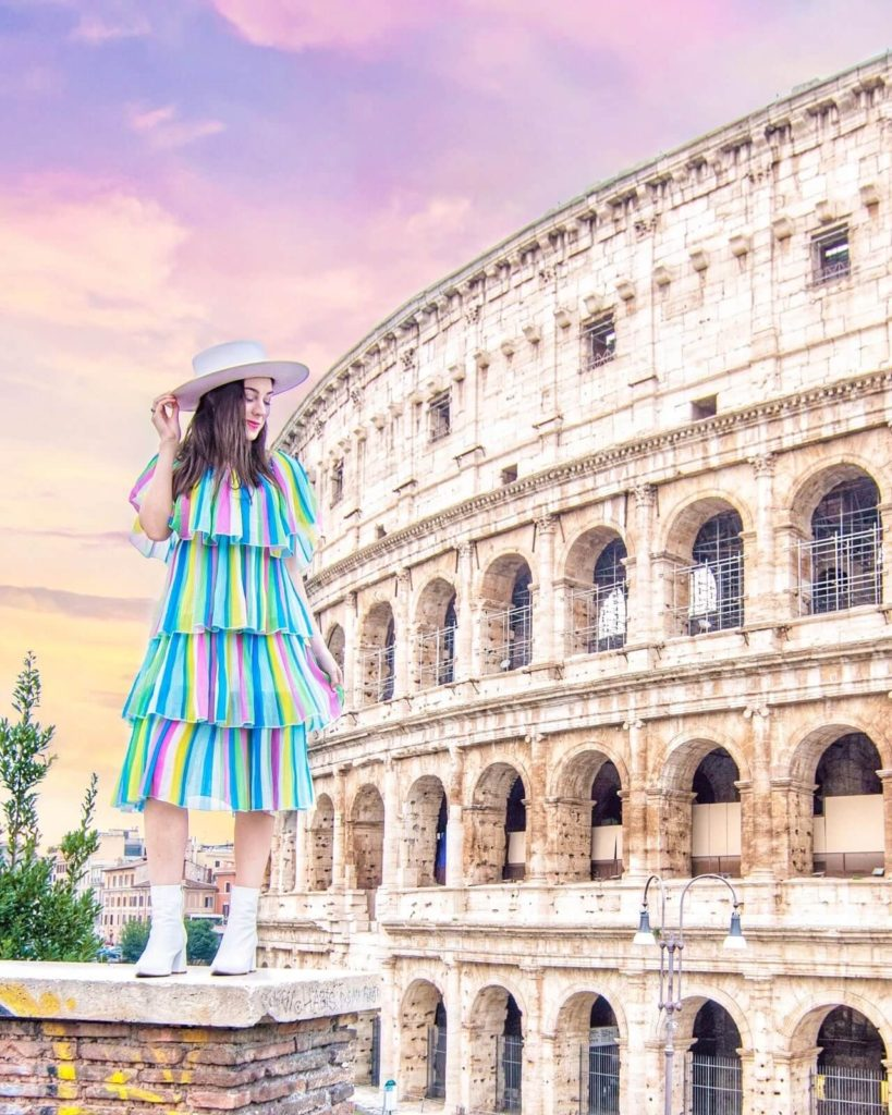 Girl standing in front of the Colosseum in Rome, Italy.