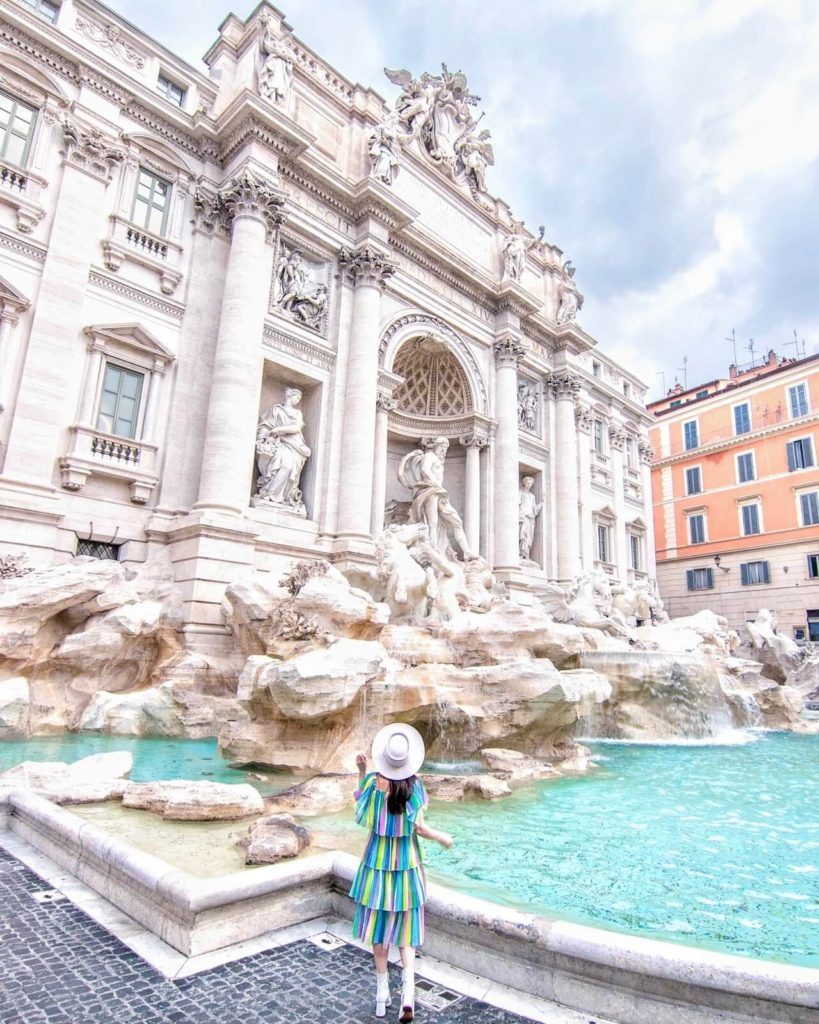 Girl standing in front of the Trevi Fountain in Rome, Italy.