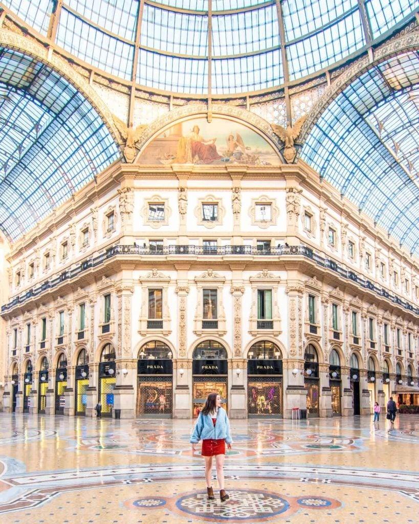 Girl walking in front of the Galleria Vittorio Emanuele II in Milan, Italy.