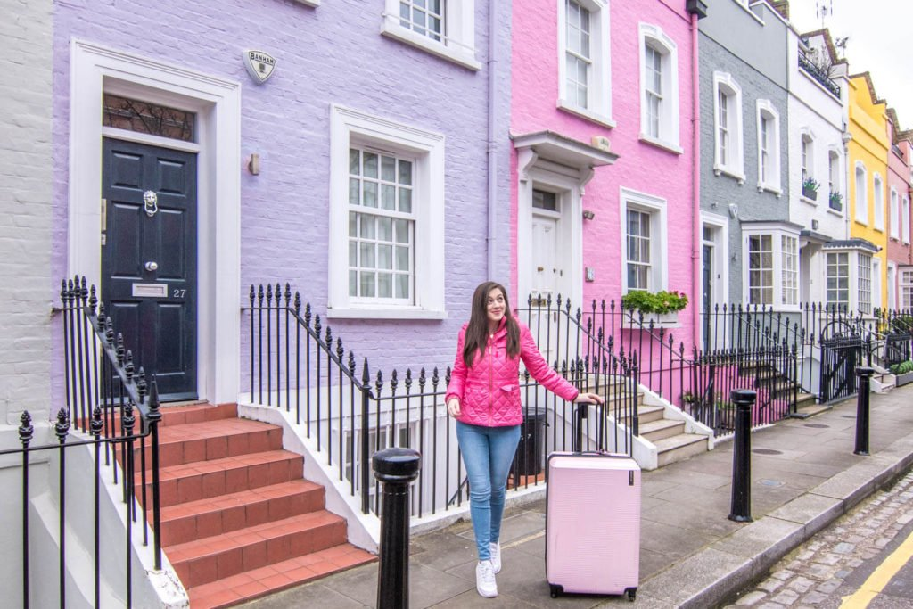 Girl with suitcase in front of colorful homes on Bywater Street in Chelsea