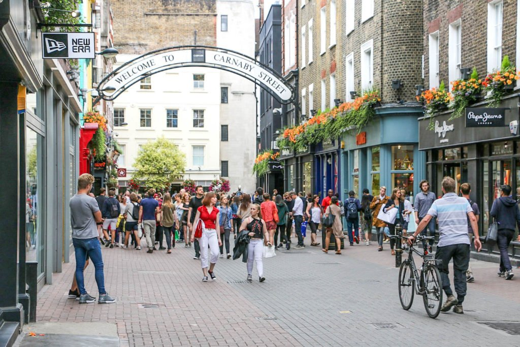 A view of the Carnaby Street welcome sign and some shops