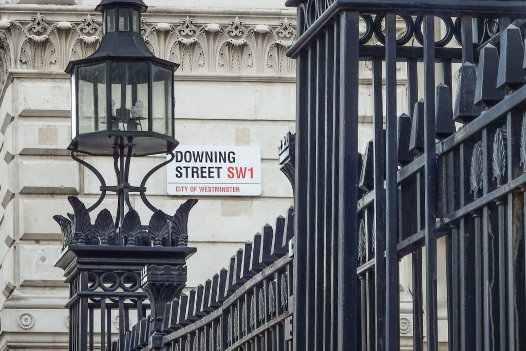 A view of the gates and street sign for Downing Street in London