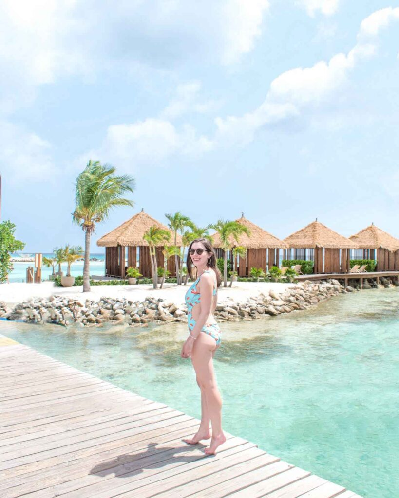 Woman walking across bridge in front of private cabanas at Renaissance Aruba Private Island